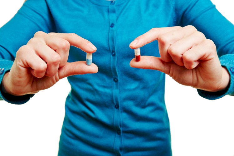 Man Holding Two Different Capsules