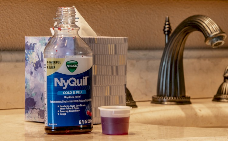 NyQuil bottle on bathroom counter with dose cup