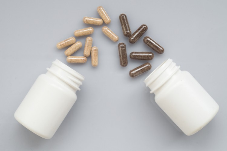 Drug capsules spill out of a two white plastic bottles