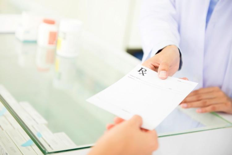 Patient Handing Prescription To Pharmacist